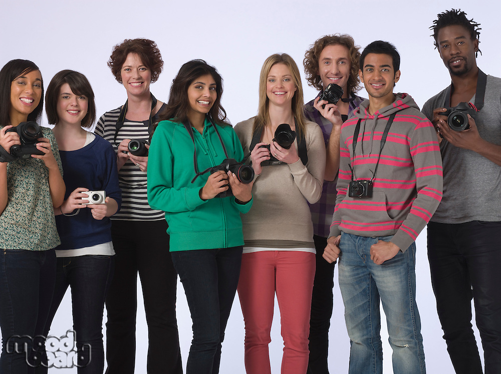 Group portrait of young people holding cameras studio shot