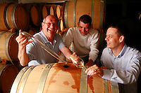 Epernay, France  in the cellars of Champagne Janisson-Baradon..Cyril Janisson (at right) with father Richard, and brother Maxence, winemakers who make Champagne in the organic traditional method, aging in oak barrels..They are tasting wine put into barrels in September 2007..Epernay is a major producer of Champagne...Photo by Owen Franken for the NY Times..May 17, 2008.May 17, 2008