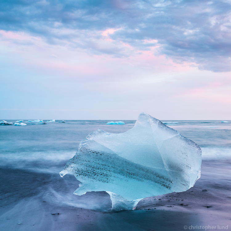 An Iceberg at the beach of Jökulsárlón Glacial Lagoon, Southeast Iceland. The Iceberg is standing in the black sand, on it's narrow foot, almost like a wine glass.