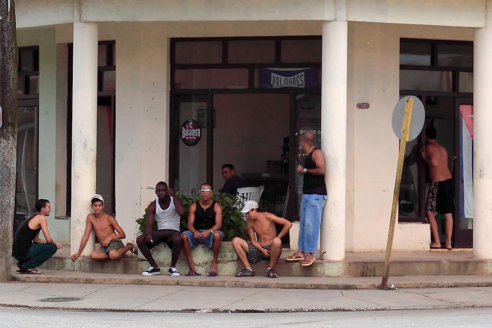 Men sitting on step in front of a bar in San Antonio de Rio Blanco, Mayabeque, Cuba.