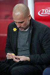 Manchester City manager Pep Guardiola takes off a yellow ribbon worn in support of Catalan independence before the game begins