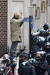 "© Licensed to London News Pictures . 11/06/2013 . London , UK . A man stands on railings surrounded by police and gives a v for victory sign . Police surround a former police station on 40 Beak Street , Soho this morning (11th June) which has been occupied by organisers as a base for today's "" Stop G8 "" anti capitalist protest . Demonstrations in London today (Tuesday 11th June 2013) ahead of Britain hosting the 39th G8 summit on 17th/18th June at the Lough Erne Resort , County Fermanagh , Northern Ireland , next week . Photo credit : Joel Goodman/LNP"