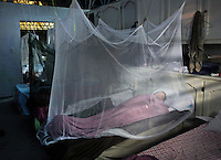 Exhausted medical volunteers sleep under mosquito netting after a day's work at Hospital Sacre Coeure in Milot, Haiti.