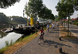 Tourists from Germany enjoy a Boat and Bike tour through Flanders. The tour guide leads the group on their morning ride from Bruges to Damme, in the Flemish region of Belgium, on Sunday, July 11, 2010. (Photo © Jock Fistick)