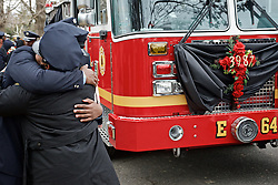 Philadelphia, PA, USA - December 13, 2014; On Ivy Hill Cemetery in Philadelphia firefighters attending the funeral of firefighter Lt. Joyce Craig-Lewis embrace next to a fire truck. The batch number of the fallen firefighter is placed on the front of the Philadelphia Fire Dept. Engine 64 truck. (photo by Bas Slabbers)<br /> <br /> <br /> Scene from Ivy Hill Cemetery in Philadelphia during the funeral of Lt. Firefighter Joyce Craig-Lewis who died in the line of duty fighting a blaze in the West Oak Lane Section of the city.<br /> <br /> Posthumously promoted to Lieutenant, Firefighter Joyce Craig-Lewis of the Philadelphia Fire Dept. was laid to rest at Ivy Hill cemetery on December 13, 2014. Lt. Craig-Lewis of Engine Company 64 is the first female firefighter of the Philadelphia Fire Dept. who has died in the line of duty. The fire department of Philadelphia is the oldest in the nation.
