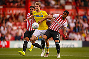 Leeds United forward Patrick Bamford (9) on the ball between Brentford defender Julian Jeanvier (23) and Brentford defender Ezri Konsa (26) during the EFL Sky Bet Championship match between Brentford and Leeds United at Griffin Park, London, England on 22 April 2019.