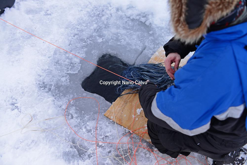 Fisherman practicing ice fishing in Lake Inari, Lapland, Finland