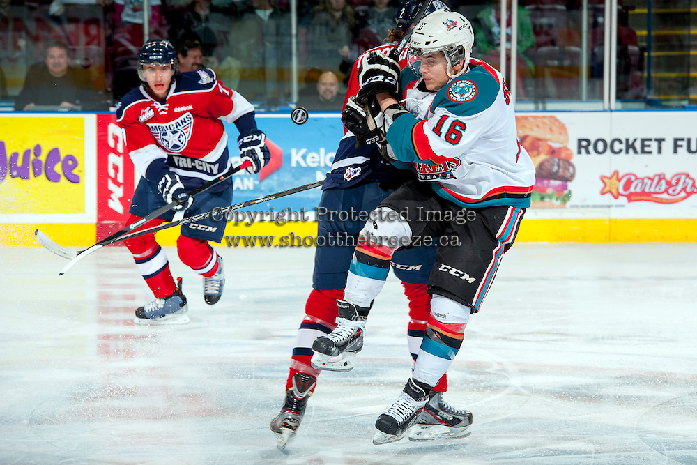 KELOWNA, CANADA - MARCH 22:Kris Schmidli #16 of the Kelowna Rockets is checked at centre ice by a player of the Tri-City Americans  on March 22, 2014 at Prospera Place in Kelowna, British Columbia, Canada.   (Photo by Marissa Baecker/Shoot the Breeze)  *** Local Caption *** Kris Schmidli;
