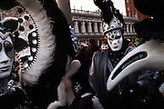 Carnival characters poses pose in costume in San Marco square in Venice.