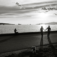 People on the seawall in silhouette with long shadows, and a small dog in the foreground.