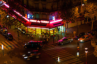 Paris, a street corner lit by a neon sign at night.