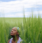 Young woman sitting in wheat field with eyes closed, close-up