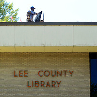 A worker removes a piece of old roofing at the Lee County Library to prep it for new a new roof in Tupelo Thursday afternoon.