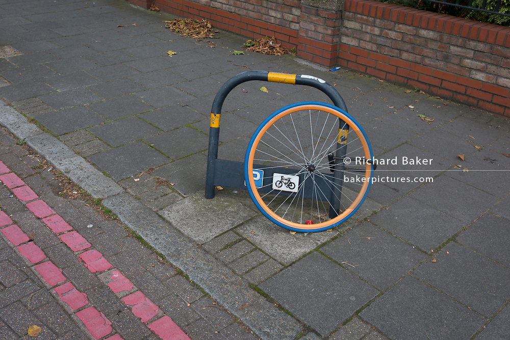 After the rest of the bike has been stolen, a lone wheel remains locked to a bike stand, on 11th September, 2017, in London, England.