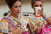 25 MARCH 2010 - BANGKOK, THAILAND: Dancers drink their McDonald's soft drinks while they wait to perform at the Erawan Shrine in Bangkok. The Erawan Shrine (Thai: San Phra Phrom) is a Hindu shrine in Bangkok, Thailand that houses a statue of Phra Phrom, the Thai representation of the Hindu creation god Brahma. The Erawan Shrine was built in 1956 as part of the government-owned Erawan Hotel to eliminate the bad karma believed caused by laying the foundations on the wrong date. The hotel's construction was delayed by a series of mishaps, including cost overruns, injuries to laborers, and the loss of a shipload of Italian marble intended for the building. Furthermore, the Ratchaprasong Intersection had once been used to put criminals on public display. An astrologer advised building the shrine to counter the negative influences. The Brahma statue was designed and built by the Department of Fine Arts and enshrined on 9 November 1956. The hotel's construction thereafter proceeded without further incident.      PHOTO BY JACK KURTZ