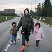 Morning, Tuesday, 15 September 2015. Aysha walks at dawn with her two daughters from Nickelsdorf refugee temporary shelter to a petrol station where they could take a taxi to Vienna.