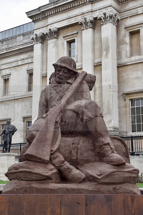 """© Licensed to London News Pictures. 25/07/2017. London UK. London, UK.  25 July 2017.  A sculpture called """"The Mud Soldier"""", by the artist Damian Van Der Velden, a graduate of the Royal Academy of Arts of The Hague, is unveiled in Trafalgar Square.  Crafted with sand mixed with mud from Passchendaele, Flanders Fields, Belgium, this artwork will be displayed for four days to mark the centenary of Passchendaele and those who lost their lives in the Great War.  The artwork will slowly dissolve away as it is exposed to rain. Photo credit : Stephen Chung/LNP"""