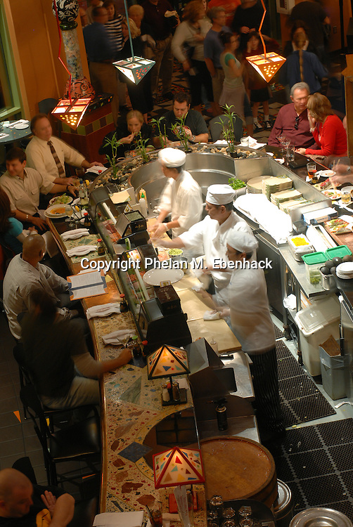 Chefs prepare sushi dishes for a usual dinner crowd at the Wolfgang Puck Cafe in Lake Buena Vista, Florida.