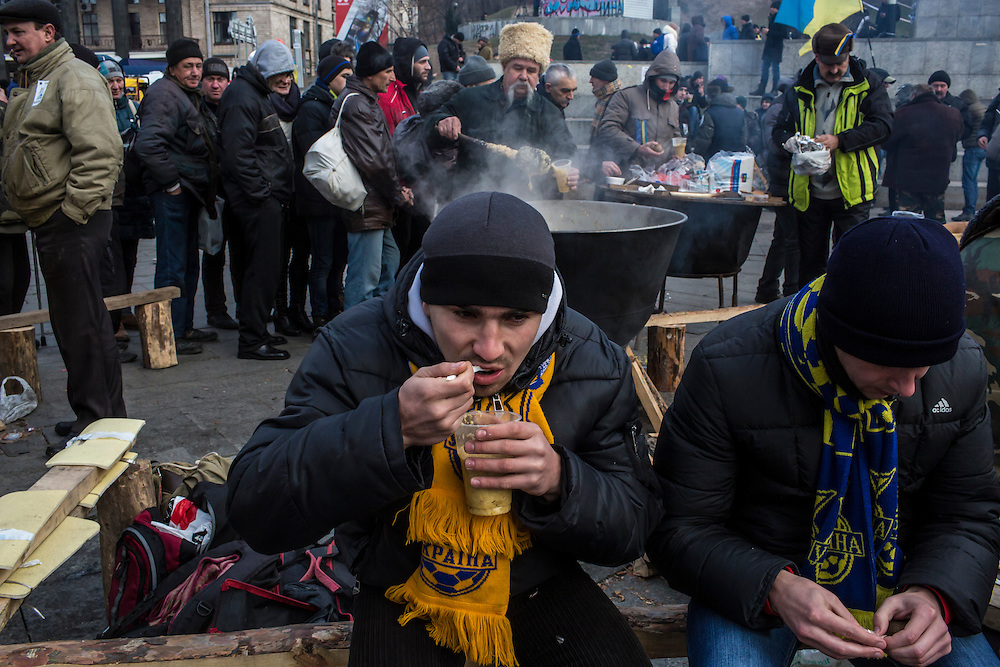 KIEV, UKRAINE - DECEMBER 4: Anti-government protesters eat soup while rallying in Independence Square on December 4, 2013 in Kiev, Ukraine. Thousands of people have been protesting against the government since a decision by Ukrainian president Viktor Yanukovych to suspend a trade and partnership agreement with the European Union in favor of incentives from Russia. (Photo by Brendan Hoffman/Getty Images) *** Local Caption ***