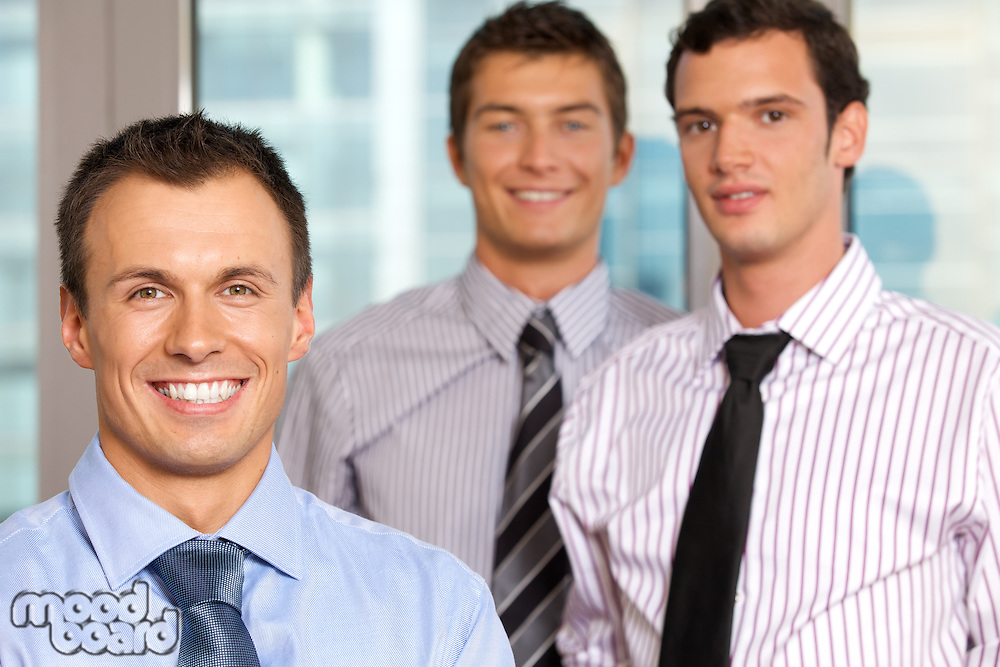 Three businessmen smiling at office, portrait