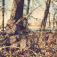 duck hunter in the brush shooting at ducks