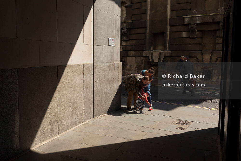 The parents of a small child in Lombard Street in the City of London, the capital's financial district aka the Square Mile, on 15th May 2018, in London, UK.