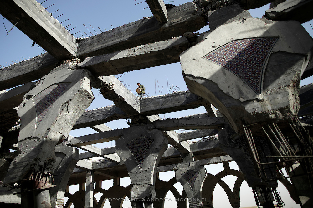 A teenager collects rubble from the roof of the main terminal at Yasser Arafat International Airport in southern Gaza.