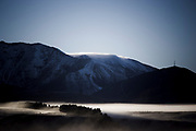 View of early morning mists and clear blues sky, Little Mount Ida with TV tower on right, Maniototo, Otago, New Zealand.