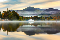 © Licensed to London News Pictures. 15/10/2018. Keswick UK. A boat & the mountains that surround Derwentwater reflect into the calm water at dawn this morning on a misty start to the day in Keswick, Cumbria. Photo credit: Andrew McCaren/LNP