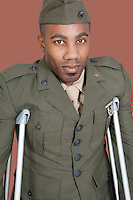 Portrait of an African American US military officer with crutches over brown background