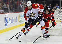 Feb 11; Newark, NJ, USA; Florida Panthers defenseman Erik Gudbranson (44) skates with the puck while being defended by New Jersey Devils right wing Cam Janssen (25) during the second period at the Prudential Center.
