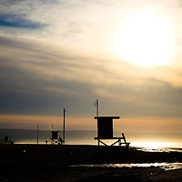 Photo of Newport Beach lifeguard towers during a colorful sunrise on Balboa Peninsula in Orange County Southern California.