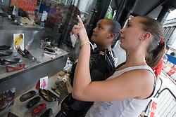 Two teenaged girls looking in a shop window,
