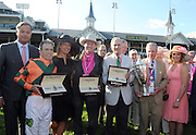 Charles Villoz, left, and Jennifer Judkins, third left, of Longines, along with Longines Ambassador of Elegance and World Alpine Cup skier Mikaela Shiffrin, right, present jockey Kerwin Clark, trainer Larry Jones and owner Brereton Jones, left to right, with their Longines timepieces after their horse Lovely Maria won the Longines Kentucky Oaks, Friday, May 1, 2015, in Louisville, Ky. Longines, the Swiss watch manufacturer known for its luxury timepieces, is the Official Watch and Timekeeper of the 141st annual Kentucky Derby.  They are joined by Brereton Jones' partner Tim Thornton, second right, holding the Kentucky Oaks trophy  (Photo by Diane Bondareff/Invision for Longines/AP Images)