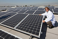 Factory worker sitting besides solar panels