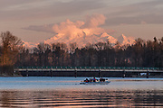 Paddling a racing canoe at sunset, lower Frasier River, Fort Langley, British Columbia.    Mount Baker in Washington state is in the background.