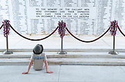 A young boy contemplates the names of the sailors that lost their lives on the USS Arizona at Pearl Harbor.