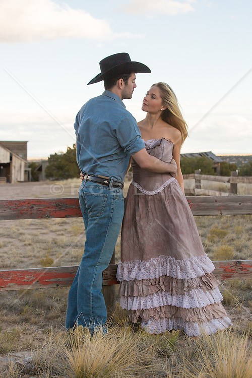 cowboy and a girl in a long prairie dress outdoors on a ranch