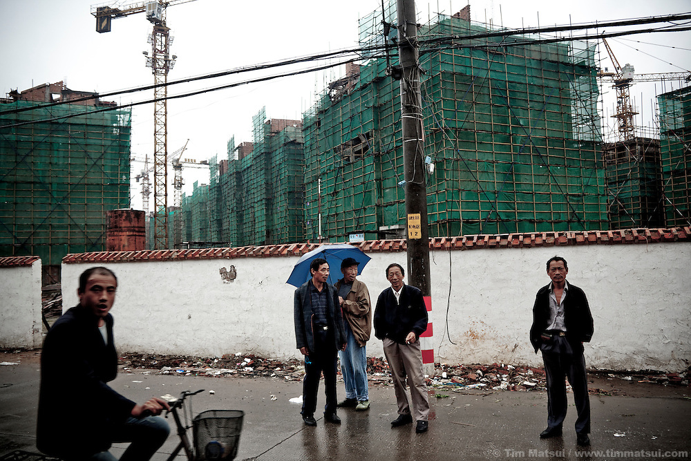 Men gather outside a construction site for new apartment blocks in Yangzhou, China, a suburb city of Shanghai and major producer of photovoltaic cells for solar power.