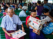 20 NOVEMBER 2017 - YANGON, MYANMAR: Men read their newspapers on the Dala Ferry. Tens of thousands of commuters ride the ferry every day. It brings workers into Yangon from Dala, a working class community across the river from Yangon. A bridge is being built across the river, downstream from the ferry to make it easier for commuters to get into the city.     PHOTO BY JACK KURTZ