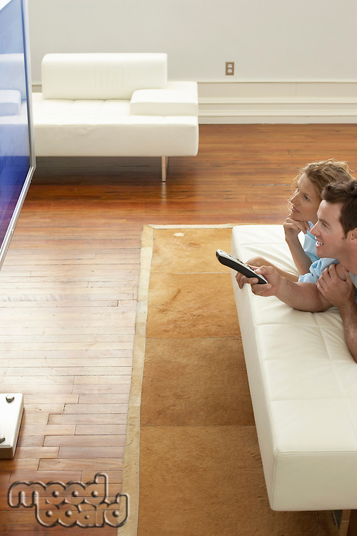 Couple lying on bed watching plasma TV together