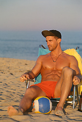 Sexy muscular volleyball player seated in a beach chair on the beach in East Hampton, NY