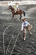 Young Juan Franco from the legendary Franco family of Charro champions, ropes a wild horse during a family practice in the Jalisco Highlands town of Capilla de Guadalupe, Mexico. The roping event is called Manganas a Pie or Roping on foot and involves a charro on foot has to rope a wild mare by its front legs and cause it to fall and roll once. The wild mare is chased around the ring by three mounted charros.
