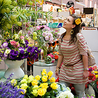 A woman shops for flowers at a stand in the historic Eastern Market in Washington, DC.