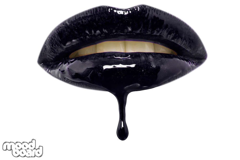 Close-up of black lip-gloss dripping from woman's lips over white background