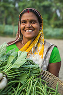 (L-R) Vegetable farmer Bindu Devi, a member of a Farmer's Producer Group, carry their vegetables in a basket to the local market in Machahi village, Muzaffarpur, Bihar, India on October 26th, 2016. Non-profit organisation Technoserve works with women vegetable farmers in Muzaffarpur, providing technical support in forward linkage, streamlining their business models and linking them directly to an international market through Electronic Trading Platforms. Photograph by Suzanne Lee for Technoserve