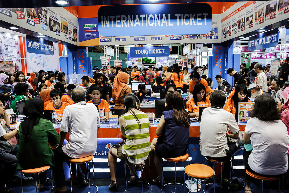 JAKARTA - INDONESIA; SATURDAY, SEPTEMBER 13, 2014; INDONESIA ECONOMIC RISING: Jakarta citizens crowd around a travel booth during travel fair at Jakarta Convention Center in Jakarta, Indonesia, Saturday, September 13, 2014. By the rising of annual income per capita has affected the expenditure of middle class in traveling. Each travel agent compete each other in giving good prices and services to customers. According to Asian Development Bank's 2014 report, Indonesia economy growth potential is in creative industry after for years relies heavily on natural resources such as mineral mining and palm oil. By the presidency of Joko Widodo, as a product of the third people election after the People Power Revolution in 1998, Indonesia is more confident in the economy growth and optimistic to become equal in quality to Brazil and China's economy growth. The emerging of Indonesia economy for the last one and a half decade after the end of Suharto's Dictatorship has been in significant way, the per capita growth has reached 400% under Susilo Bambang Yudhoyono presidency. Indonesia is home for 74 million of middle class as estimated by Boston Consulting Group, and  will double in 2020.
