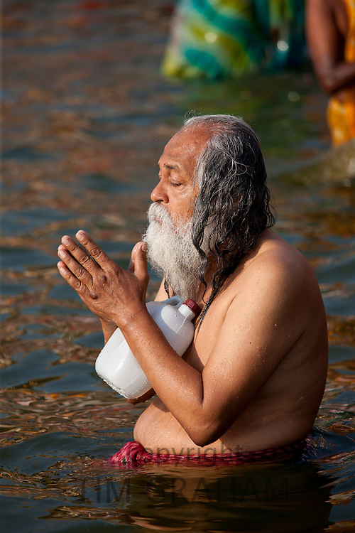 Indian Hindu pilgrim bathing and praying in The Ganges River at Dashashwamedh Ghat in Holy City of Varanasi, India