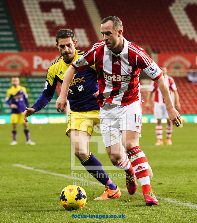 Charlie Adam (centre right) of Stoke City looks to clear the ball away from danger during the Barclays Premier League match at the Britannia Stadium, Stoke-on-Trent<br /> Picture by Tom Smith/Focus Images Ltd 07545141164<br /> 12/02/2014