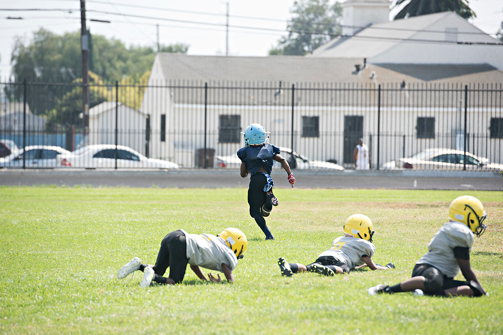 "Cerritos Vypers defenders lay in wake as Maxwell ""Bunchie"" Young, 10, scores one of his three touchdowns three during his team's 31-0 win."